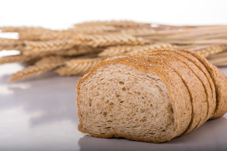 Close-up of bread on table against white background