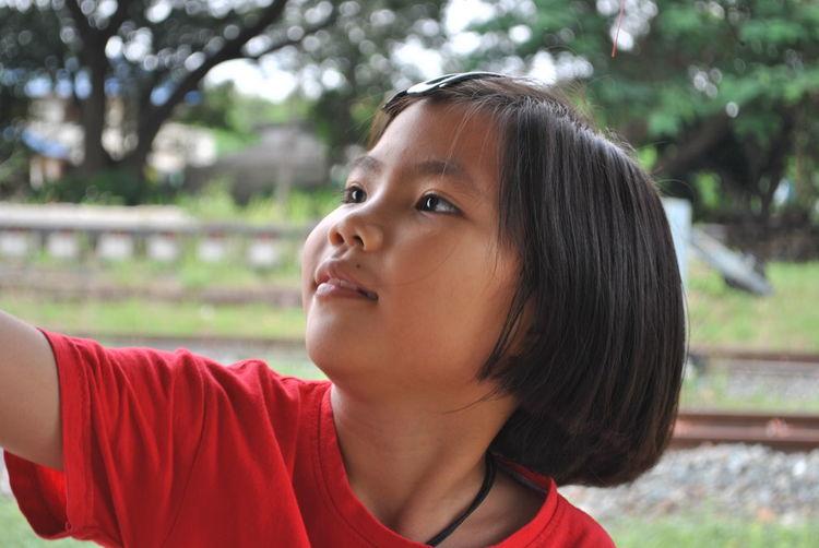 Girl looking away against trees