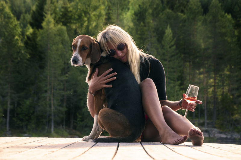 Young woman holding wineglass embracing dog on floorboard against trees