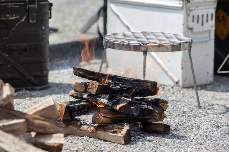 High angle view of burning firewood on field during camping