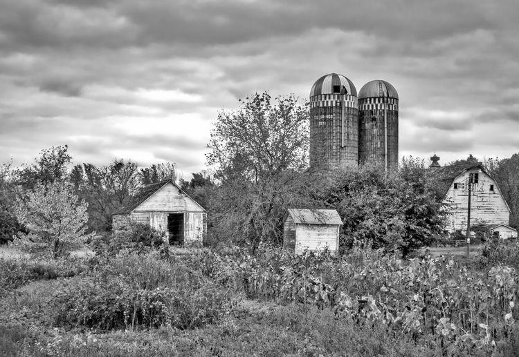 Barn and silos on field against cloudy sky
