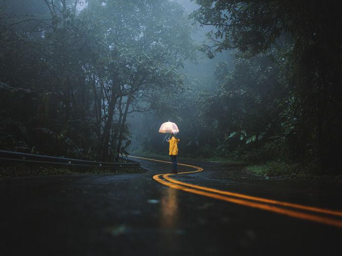 Man with umbrella on road during rainy season