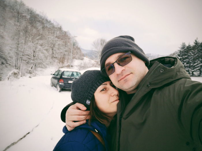Portrait of couple embracing against sky during winter