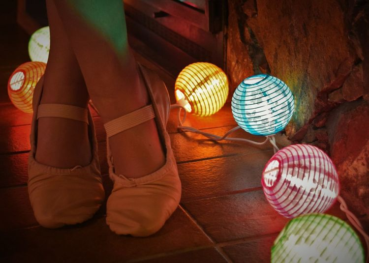 Low section of ballerina standing by illuminated lighting decoration