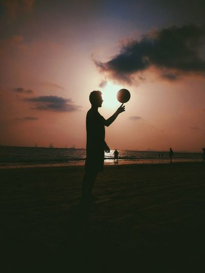 Silhouette man playing with ball at beach against sky during sunset
