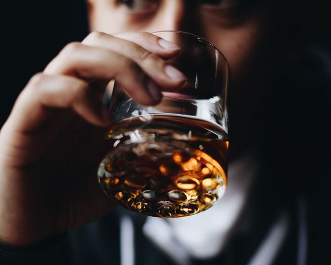 Midsection Of Man Drinking Alcohol From Glass