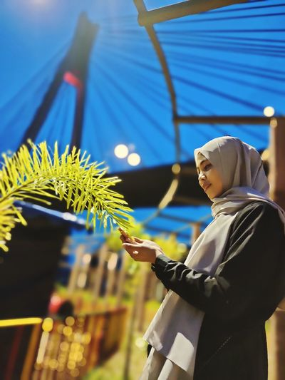 Low angle view of woman in hijab touching plant outdoors