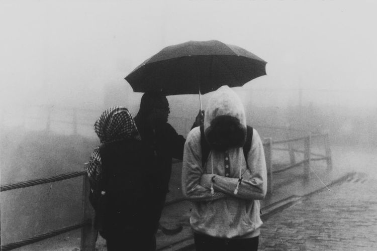 Rear view of man and woman standing in rain