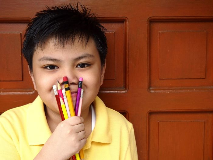 Close-Up Of Young Holding Pencils