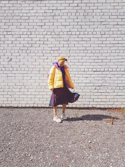 Full length of woman walking against brick wall