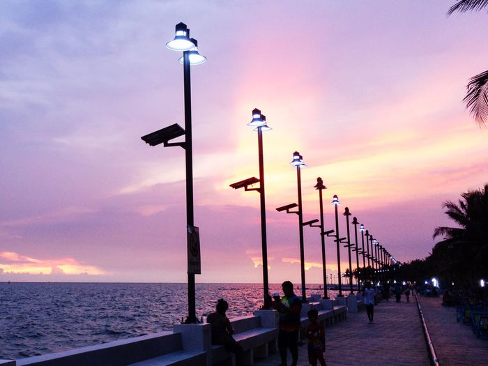 People on street by sea against sky during sunset