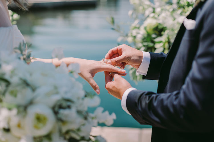 Midsection of groom putting ring on bride finger