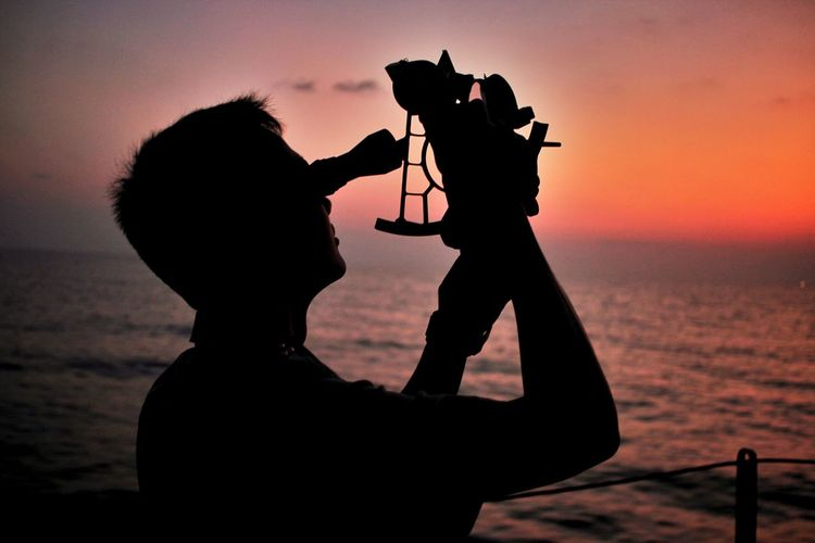 Silhouette of man using telescope against sky at sunset