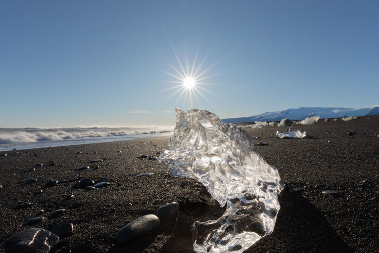 Glacial ice from Jokulsarlon glacier lagoon washed on black volcanic sand sparkles in sun on Diamond Beach, Iceland, IS, Europe Iceland Europe Ice Iceberg Jökulsárlón Jökulsárlón Glaciar Lagoon Glacier Glacial Landscape Nature Environment Tranquility Tranquil Scene Beauty In Nature No People Water Scenics - Nature Diamond Beach Diamond Beach Iceland Volcanic  Black Sand Black Sand Beach Sun Sparkles Surf Sky Sunlight Clear Sky Lens Flare Sunbeam Blue Sunny Beach Outdoors Bright
