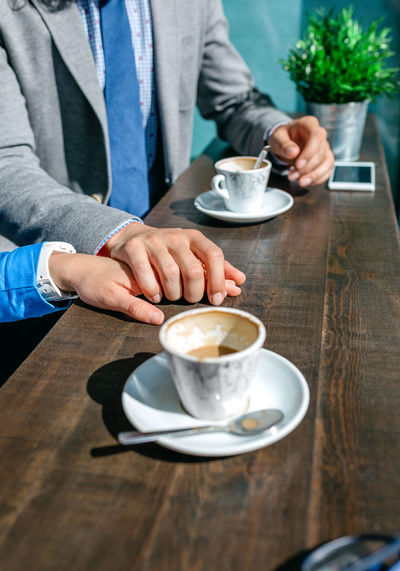 Midsection of woman holding coffee at cafe