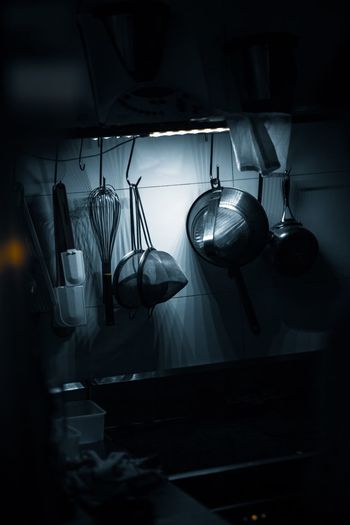 Close-up of kitchen utensils hanging at home in darkroom