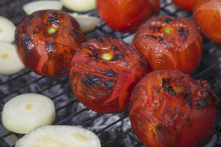 Close-up of grilled onions and tomatoes on barbecue grill