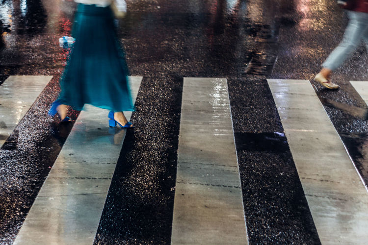 Low Section Of Woman Crossing Wet Zebra Crossing At Night