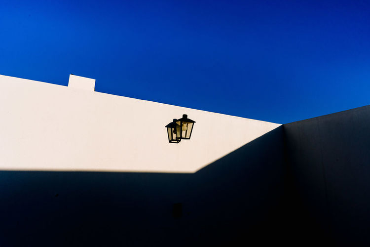 Low angle view of a lamp on building against clear blue sky