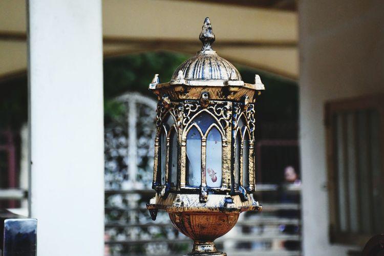 Close-up of illuminated lamp against building