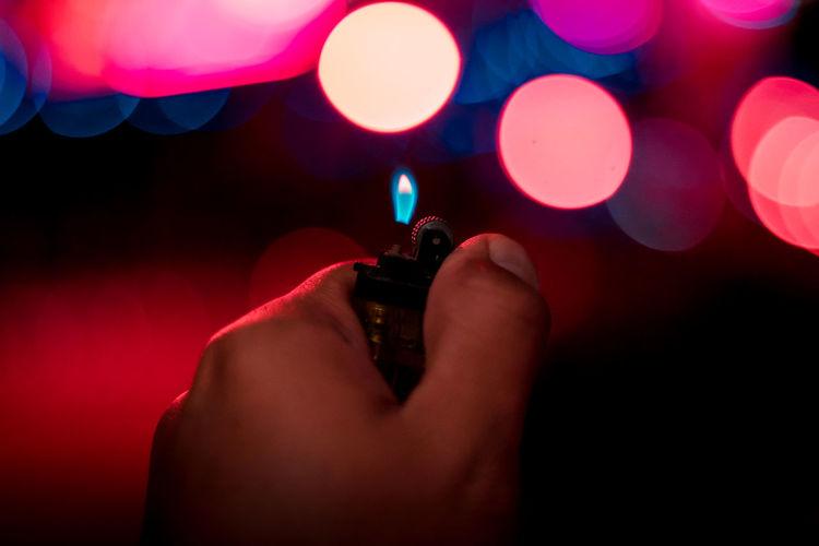 Close-Up Of Hand Holding Illuminated Cigarette