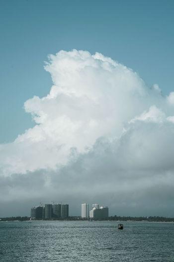 飘飘风波远钓船,朗朗白云沧海间,十里椰林今安在,万户楼盘一望间。 building Cloud - Sky Architecture Building Exterior Sea Building City Boat Water