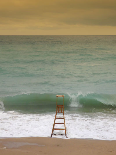 Lifeguard chair on shore at beach during sunset