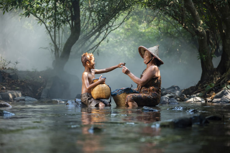 Smiling grandmother and grandson sitting with baskets in river