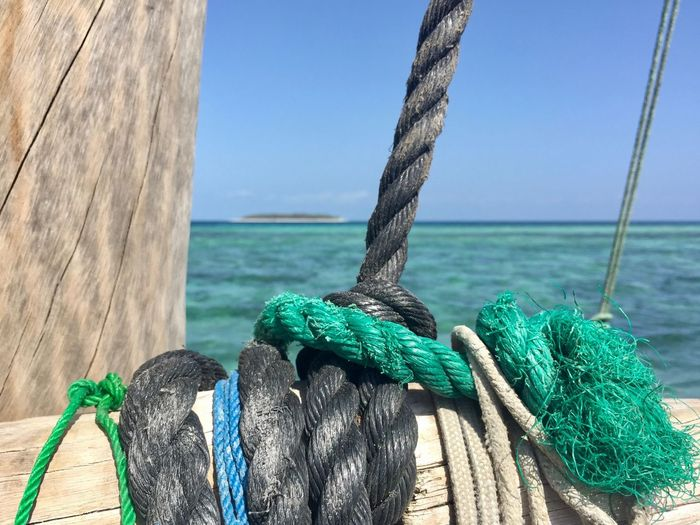 Dhow boat in Zanzibar, surrounded of beautiful coral reefs. Depending On Ocean Dhow Boat Fishing Boat Plastic Rope Rope Water Sea Tied Up Nature Sky End Plastic Pollution No People Sunlight Clear Sky Blue Close-up Turquoise Colored Focus On Foreground Outdoors Tied Knot Strength Transportation The Great Outdoors - 2018 EyeEm Awards The Traveler - 2018 EyeEm Awards Summer Sports