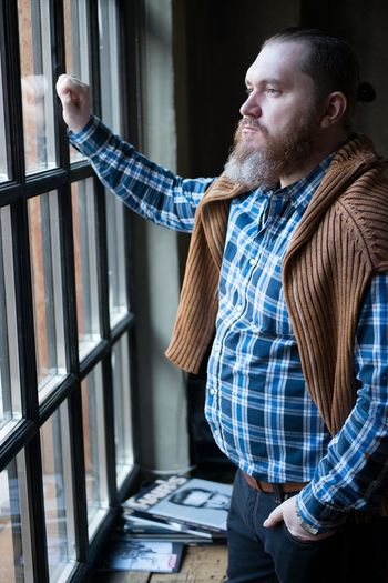 Thoughtful man wearing suspender looking through window at home