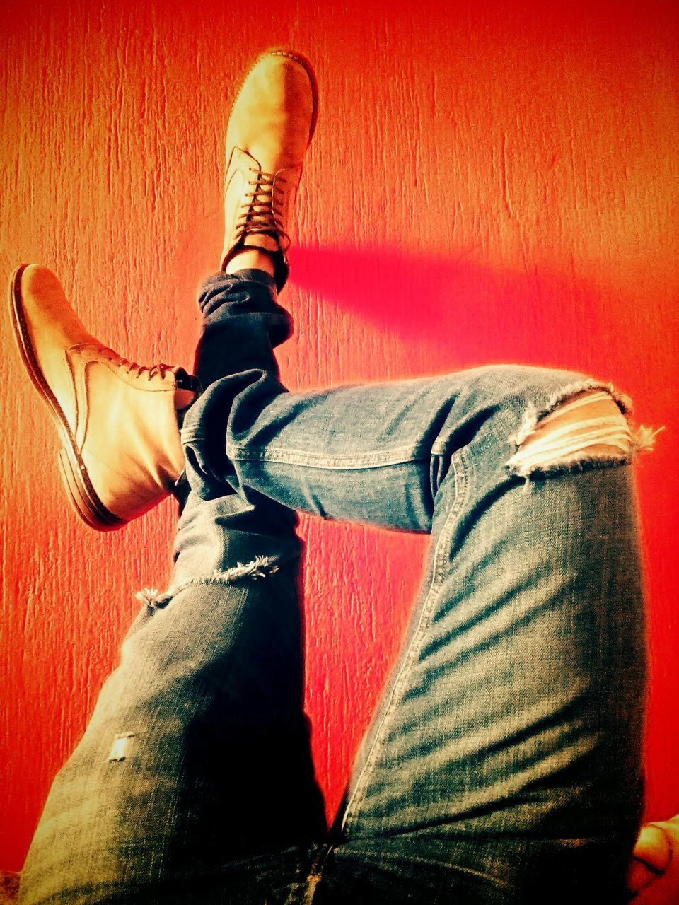 one person, jeans, low section, human leg, casual clothing, human body part, indoors, real people, men, one man only, sitting, leisure activity, lifestyles, red, close-up, human hand, only men, day, adult, people, adults only