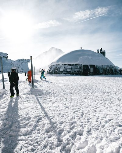 Rear view of people skiing on snowcapped mountain against sky