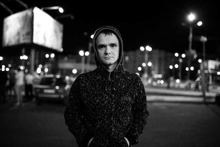 Portrait of man against illuminated street at night