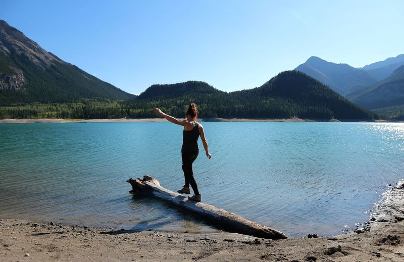Woman walking on log in lake against clear sky