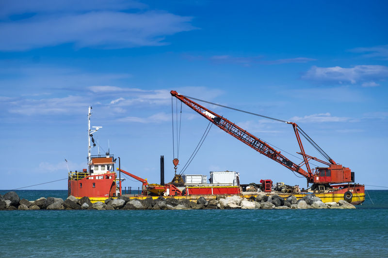Crane making rocky groynes on sea against blue sky