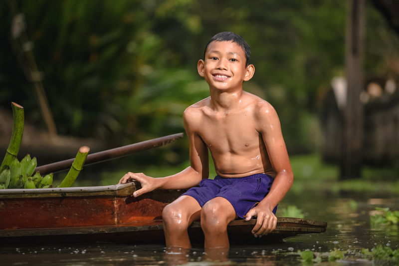 Portrait of smiling shirtless boy sitting on boat in river