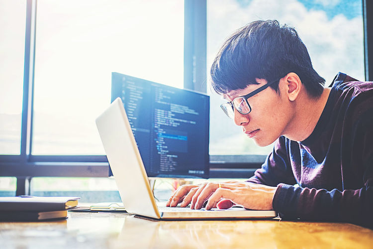 Man doing coding in laptop at office