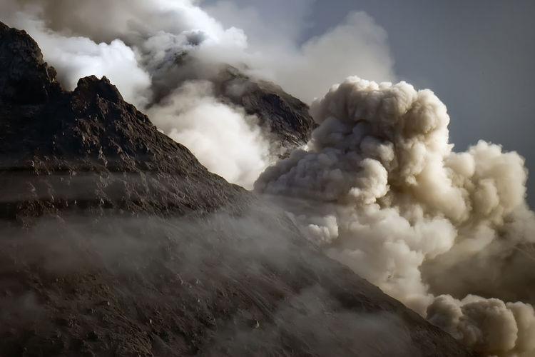 Volcano erupting against sky
