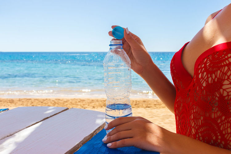 Midsection of man drinking water from beach
