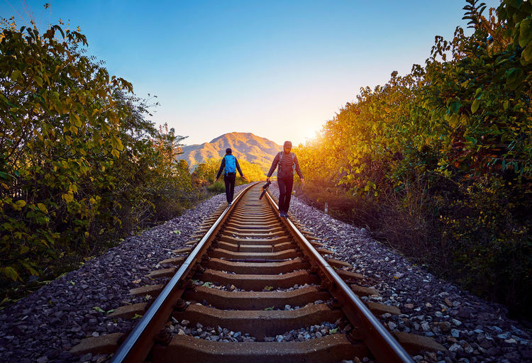 Friends Walking On Railroad Tracks Amidst Trees Against Clear Sky