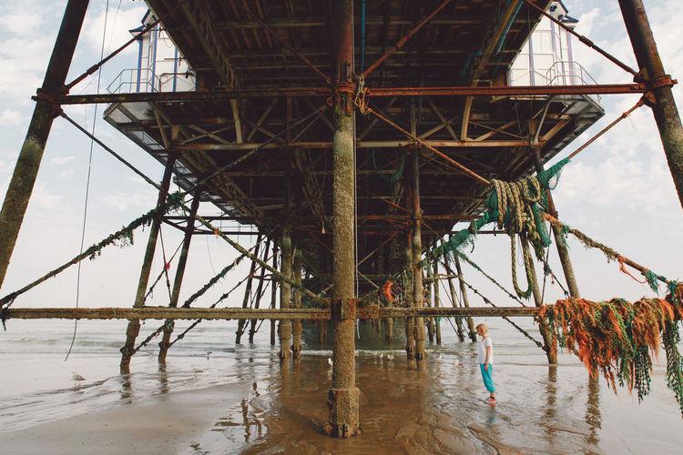 Woman standing below eastbourne pier at beach