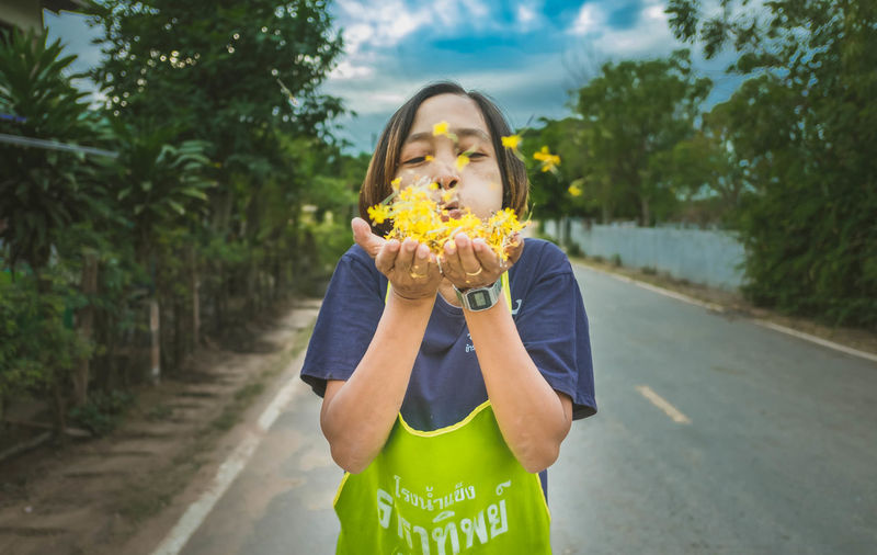 Portrait Of Woman Blowing Yellow Flowers On Road Amidst Trees