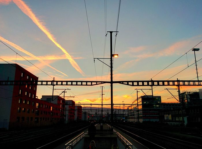 Railway Tracks Amidst Buildings Against Sky During Sunset