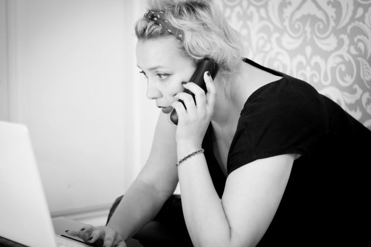 Woman talking on phone while using laptop at home