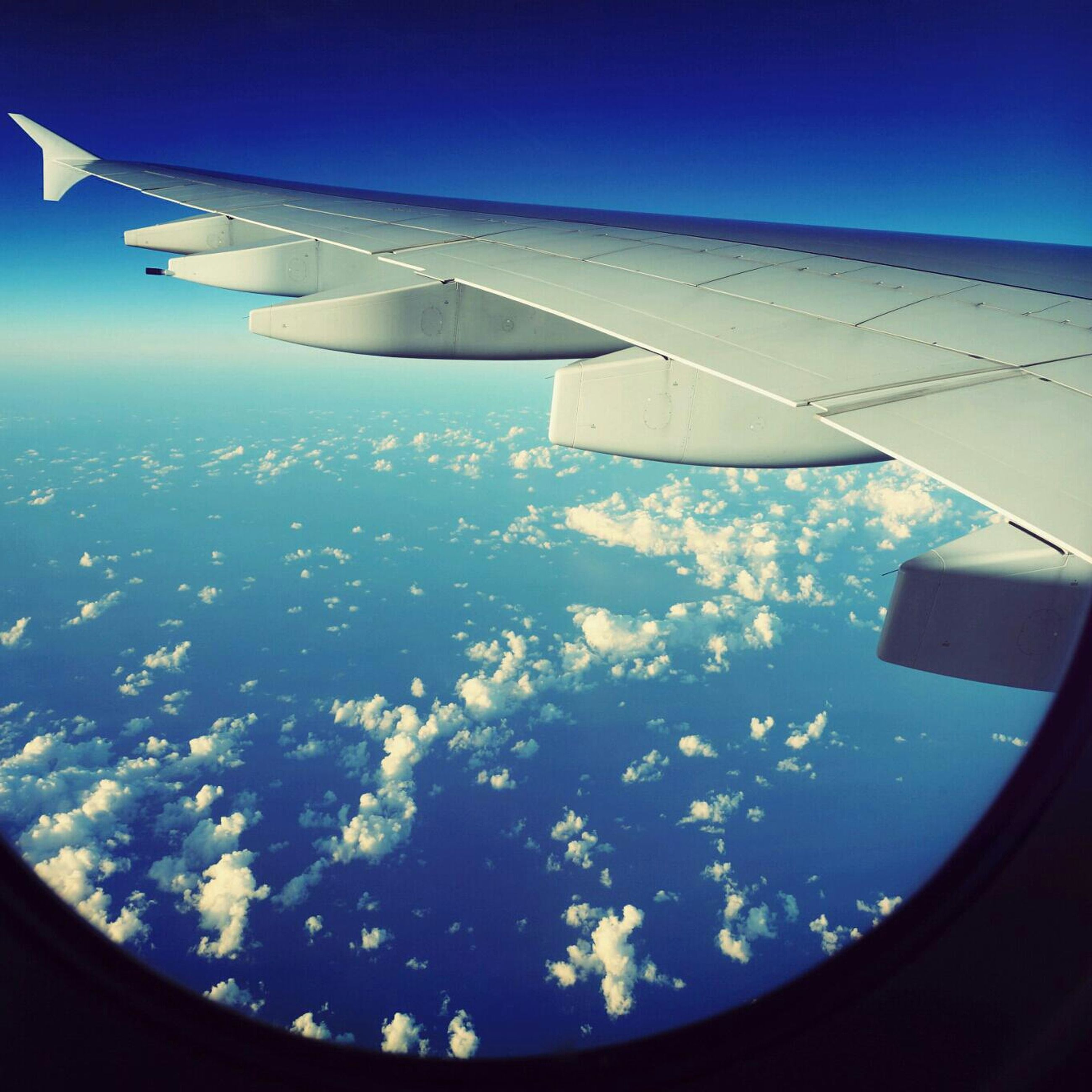 airplane, air vehicle, flying, aircraft wing, transportation, mode of transport, aerial view, part of, mid-air, cropped, sky, on the move, travel, journey, cloud - sky, public transportation, airplane wing, window, commercial airplane, aeroplane