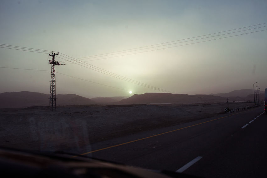 Middle East West Bank Cable Car Car Point Of View Clear Sky Connection Day Electricity  Electricity Pylon Landscape Mode Of Transport Mountain Nature No People Outdoors Road Roadtrip Sky Sunset Telephone Line The Way Forward Transportation Travel Windshield