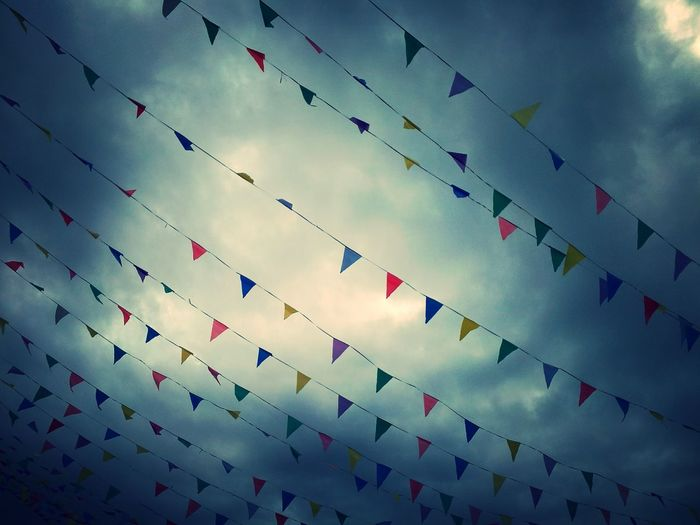 Multi colored bunting against sky