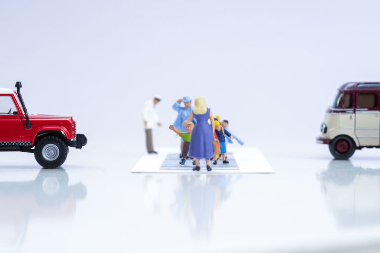 Group of people in toy car against white background
