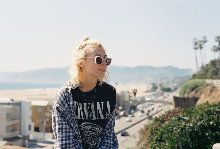 Young woman wearing sunglasses standing in city against sky