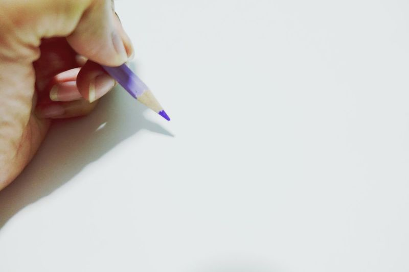Close-up of hand holding pencils against white background